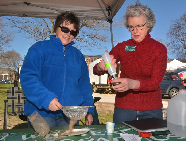 JERREY ROBERTS Michele Pietras, left, of Granby, and Christine Bergquist, of Amherst, test a soil sample at the Western Massachusetts Master Gardeners Association tent Saturday at the Amherst Farmers Market. Bergquist is a master gardener; Pietras is an intern.