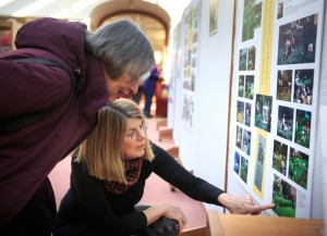 DAN LITTLE Members of the Amherst Garden Club, Carol Pope, left, and Meredith Michaels view an exhibition of photos for the 100th anniversary of the club Thursday at Jones Library in Amherst.